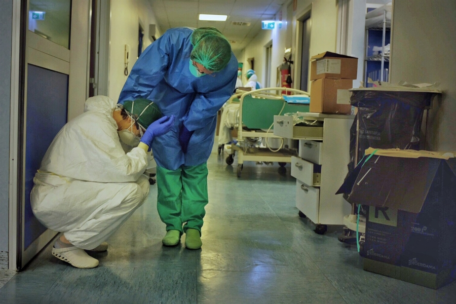 Two intensive care professionals comfort each other in the ICU of a hospital in Cremona, Italy, on Friday, March 13, 2020.